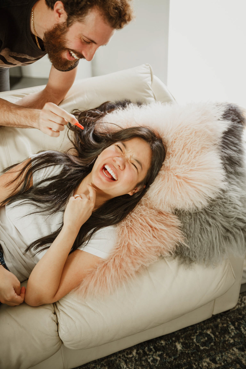 joshua tree california engagement session eda laughing on pillow-covered couch while matt tries to feed her a snack