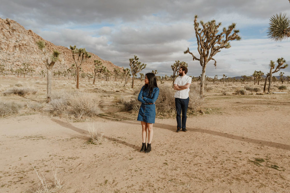 joshua tree california engagement session eda and matt standing and looking off to the side, trees in background