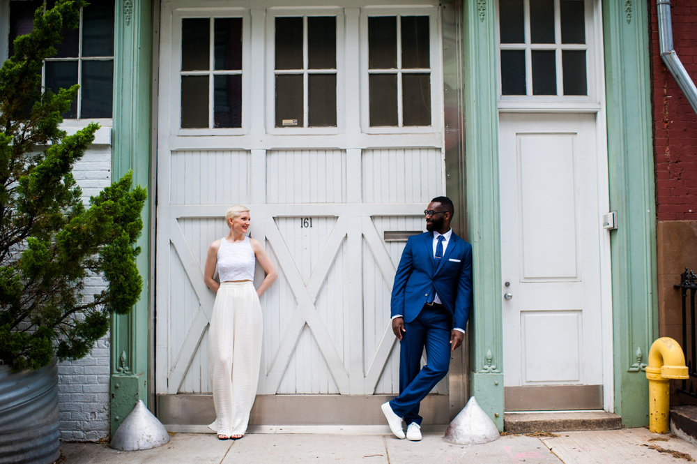 intimate new york elopement couple leaning against building, smiling at each other
