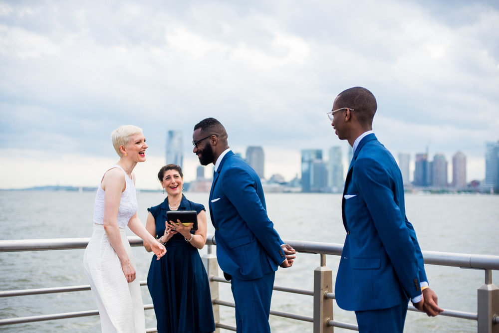 intimate new york elopement teddy, vanessa, officiant, and teddy's son laughing on pier