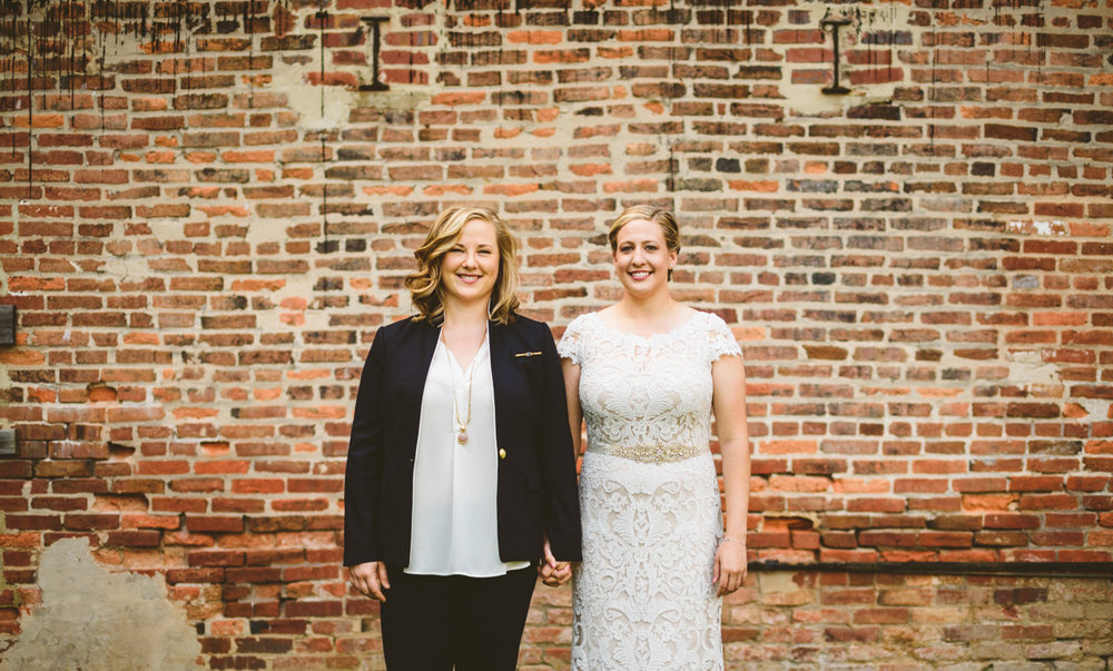 BALTIMORE WEDDING AT MOUNT WASHINGTON MILL DYE HOUSE HOPE AND MEG HOLDING HANDS IN FRONT OF BRICK WALL