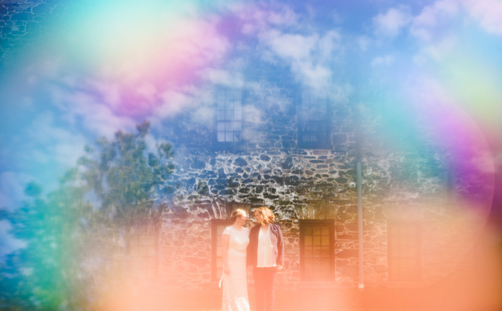 BALTIMORE WEDDING AT MOUNT WASHINGTON MILL DYE HOUSE COUPLE OUTSIDE STONE HOUSE, TRANSPARENT RAINBOW AND CLOUD OVERLAY