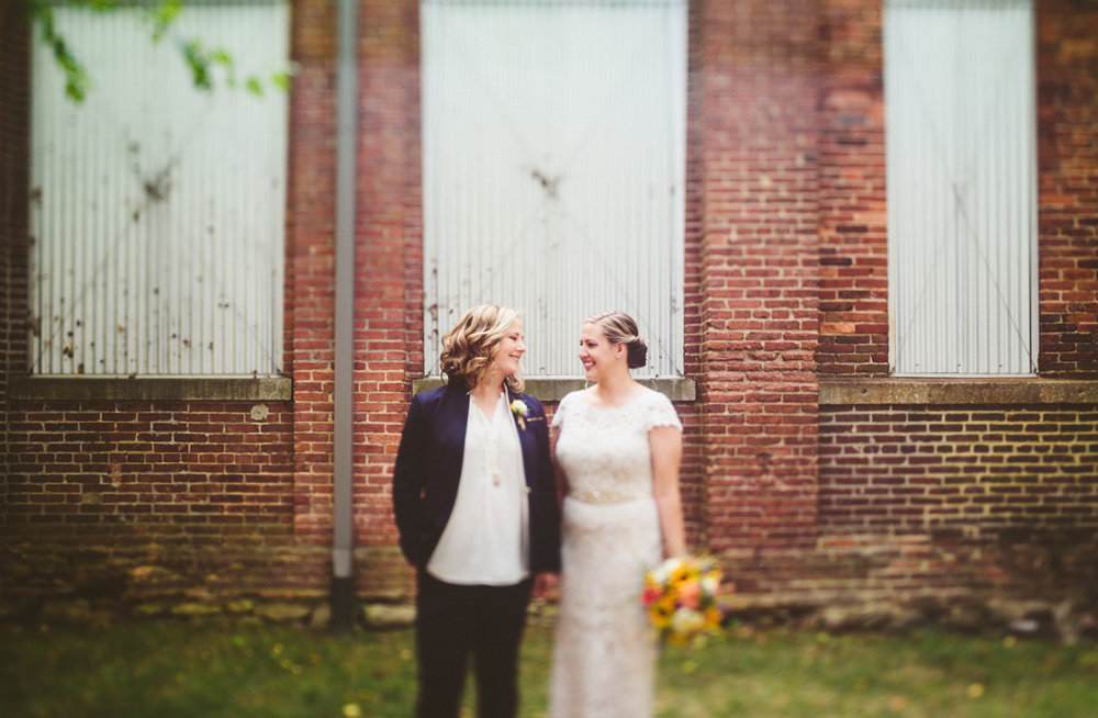 BALTIMORE WEDDING AT MOUNT WASHINGTON MILL DYE HOUSE COUPLE SMILING AT ONE ANOTHER IN FRONT OF BUILDING