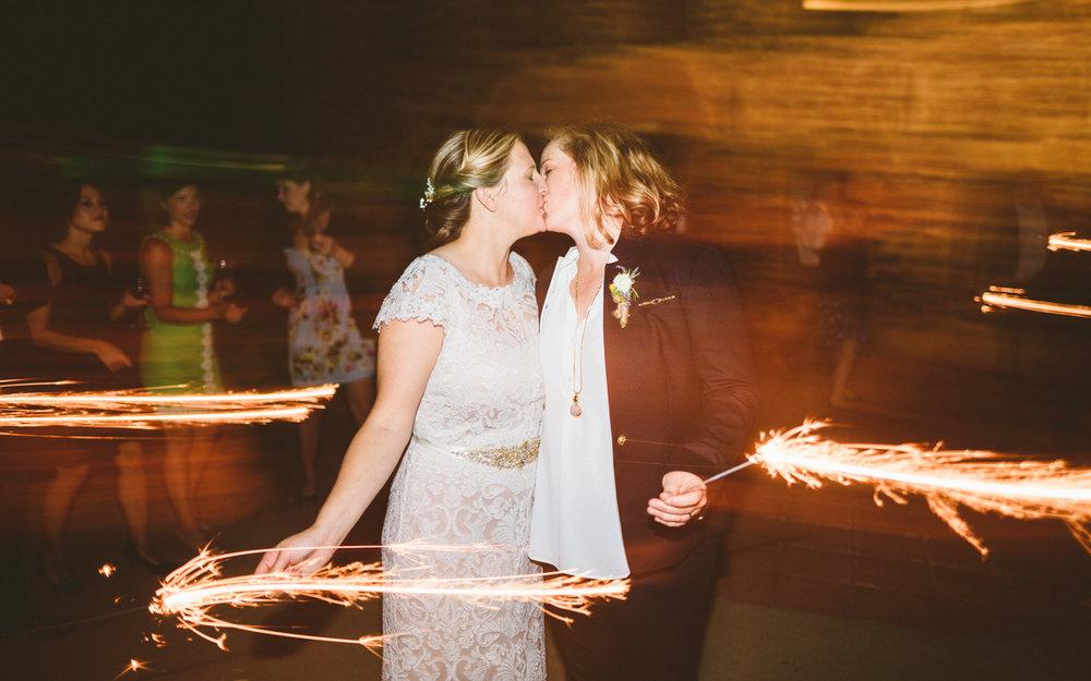 BALTIMORE WEDDING AT MOUNT WASHINGTON MILL DYE HOUSE COUPLE KISSES WHILE HOLDING SPARKLERS
