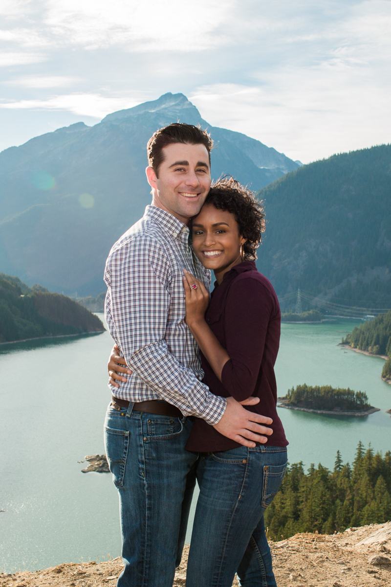 Diablo lake engagement session embrace with mountains and lake in background