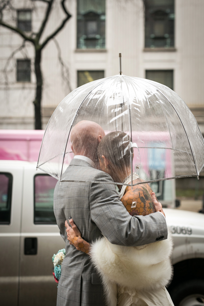 tattooed feminist elopement nyc couple embracing on sidewalk under clear umbrella