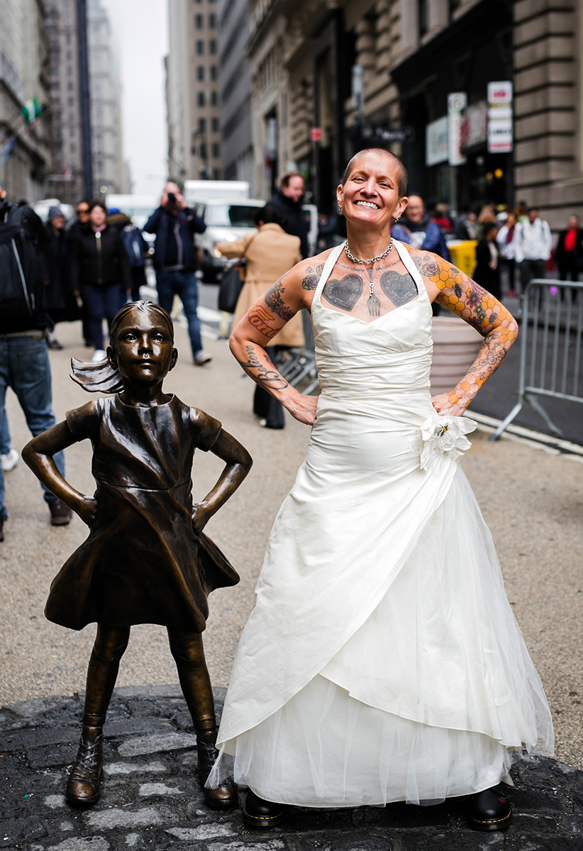 tattooed feminist elopement nyc inger with wall street's fearless girl statue