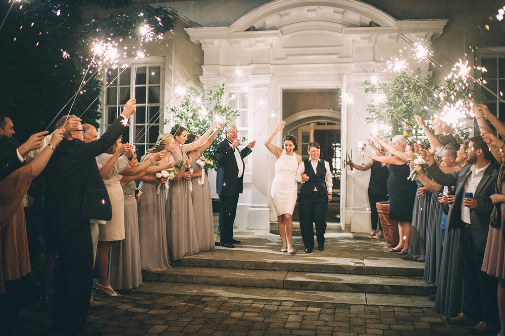 Garden wedding louisville kentucky brides leaving under sparklers held by guests