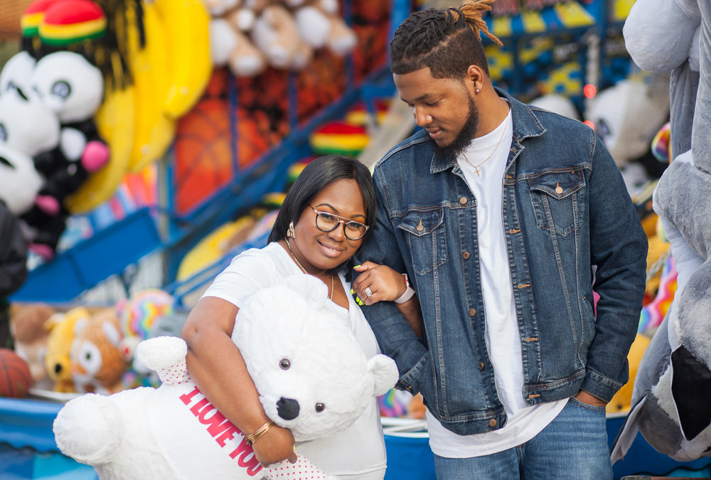 "CARNIVAL PHOTO SESSION DURHAM NORTH CAROLINA COUPLE WALKING WITH ARMS LOOPED, BRITTANY HOLDING STUFFED BEAR WEARING A T-SHIRT THAT READS ""I LOVE YOU"""