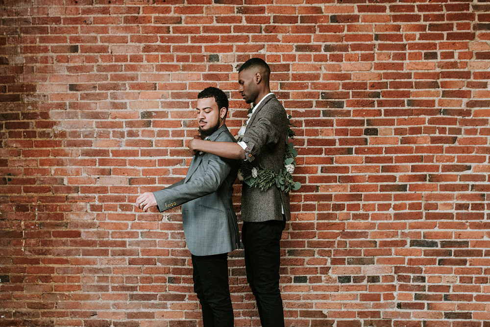 baltimore photo shoot grooms in front of brick wall