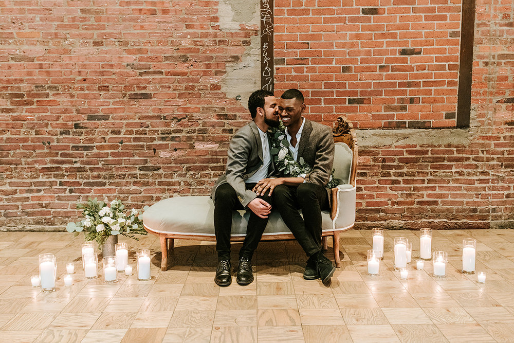 baltimore photo shoot couple on elegant couch with lit candles on floor, brick wall in background