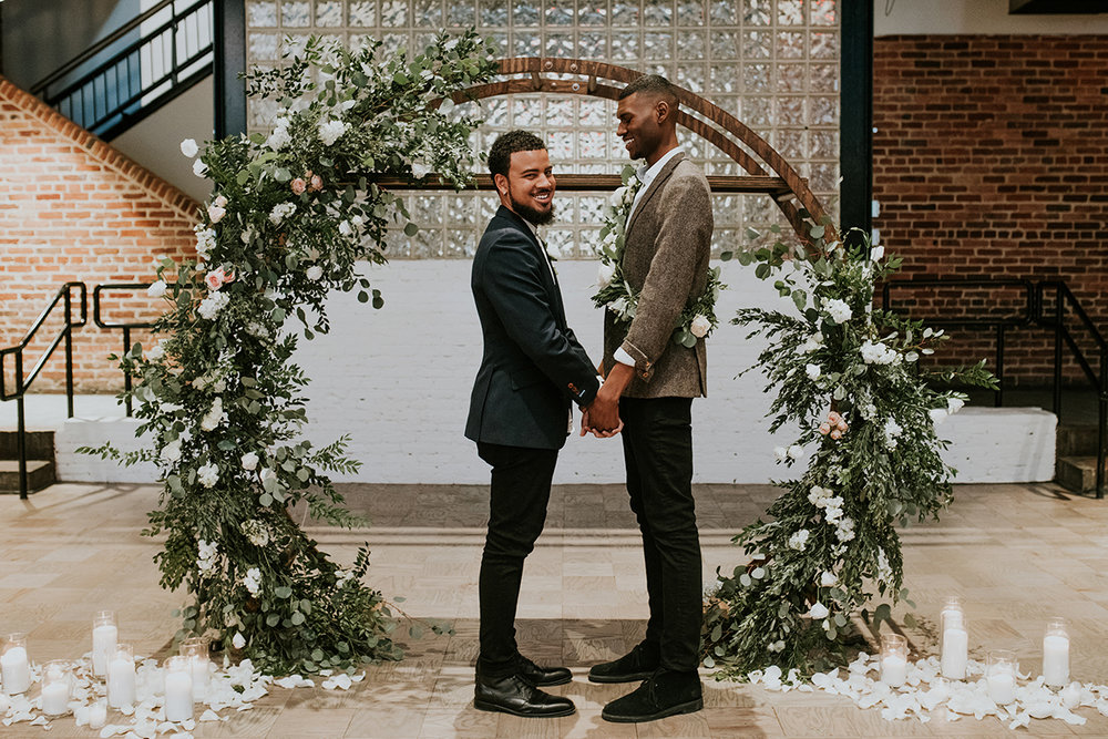 baltimore photo shoot couple at altar made with floral arrangements on large wooden semicircle arch, candles and flower petals surrounding arch