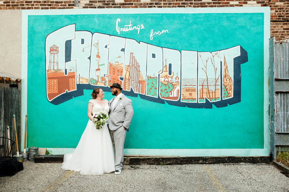 "brooklyn bar wedding abby and joey couple in front of mural reading ""Greetings from greenpoint"""