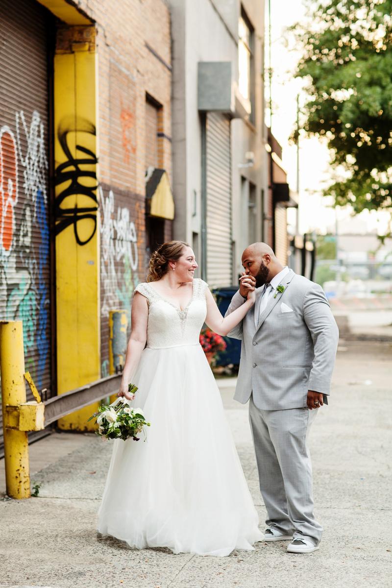 brooklyn bar wedding joey kissing abby's hand by graffitied brick