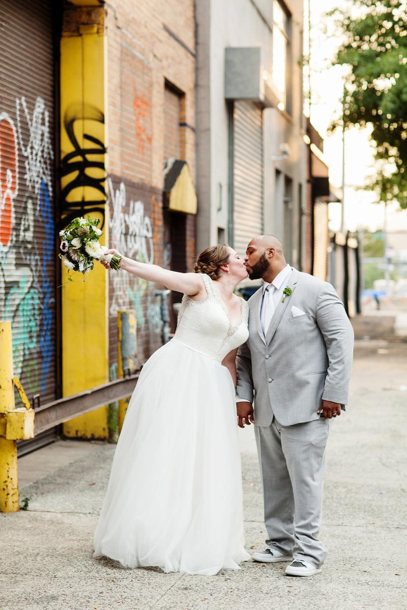 brooklyn bar wedding kiss by graffitied brick