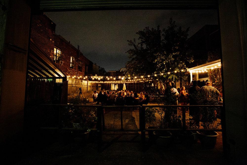 brooklyn bar wedding reception on patio lit with string lights