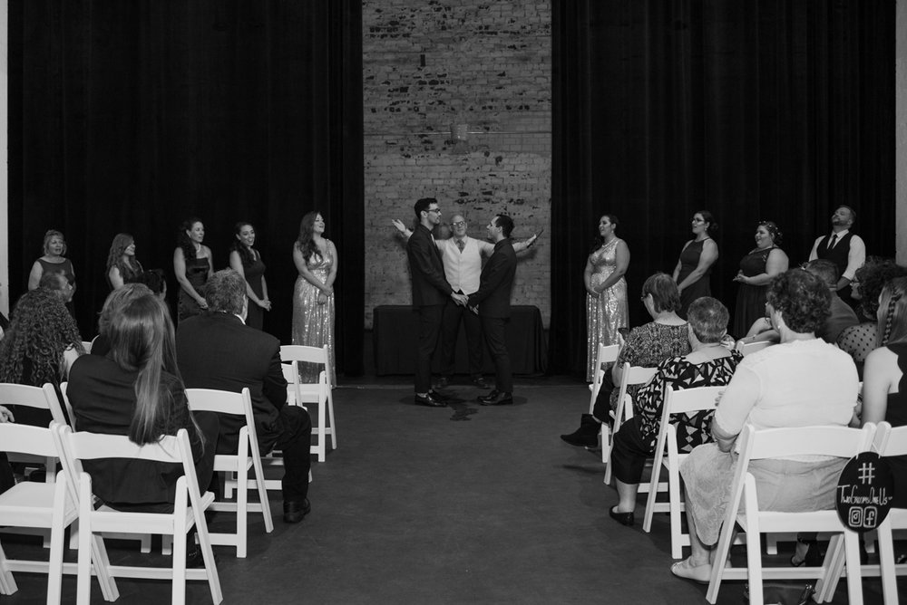 rialto theatre wedding officiant with arms out announcing newly married couple