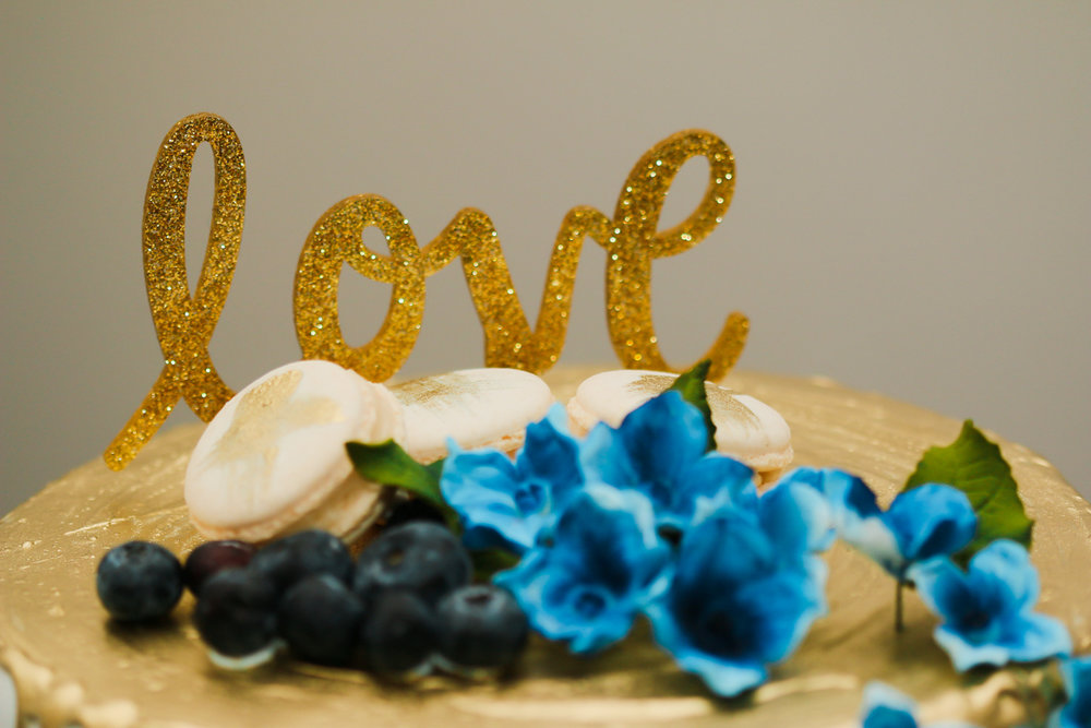 "rialto theatre wedding cake with glitter ""love"" decal, blueberries, flowers, and macaroons topping"
