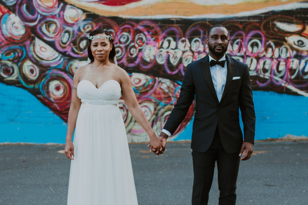 art-inspired levine museum wedding couple holding hands with mural in background