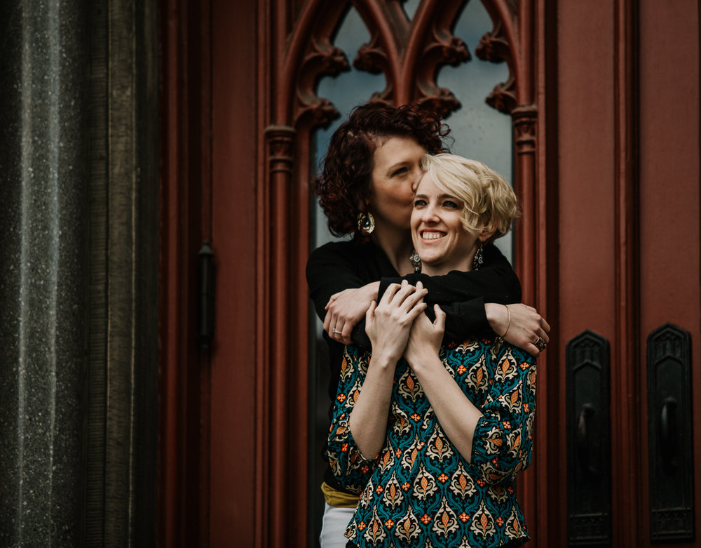 BALTIMORE COFFEE SHOP ENGAGEMENT SESSION EMBRACE IN FRONT OF ORNATE DOORS