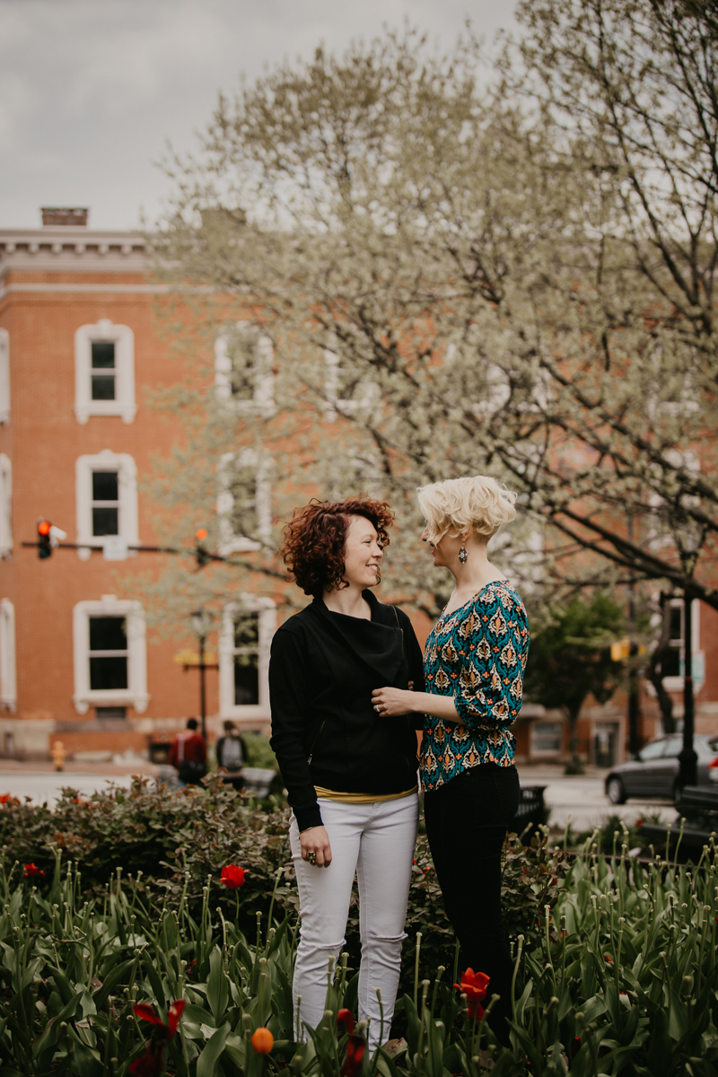 BALTIMORE COFFEE SHOP ENGAGEMENT SESSION ALI AND LIZ IN SMALL GARDEN WITH STREET IN BACKGROUND