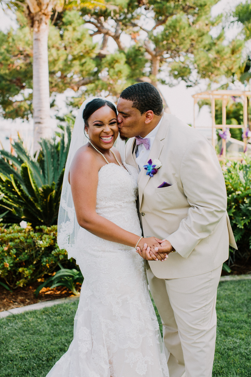 San Diego Tropical-Inspired Wedding william kissing janelle's cheek in garden