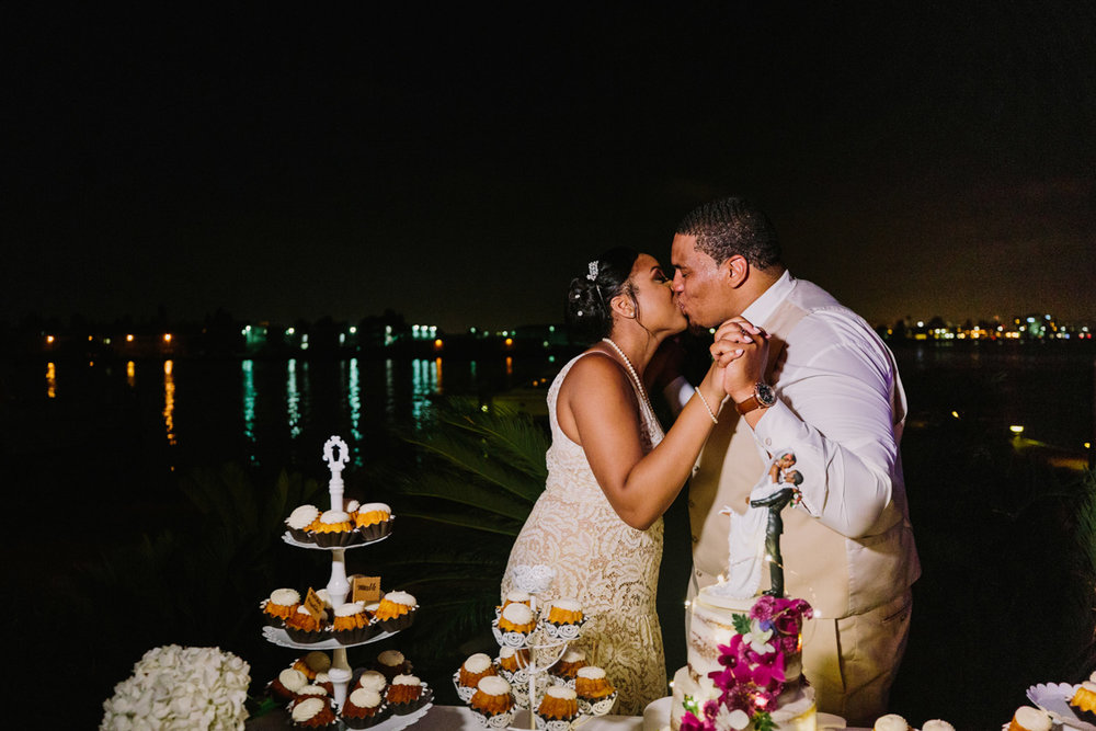 San Diego Tropical-Inspired Wedding couple kissing by dessert table with ocean and nighttime lights of city in background