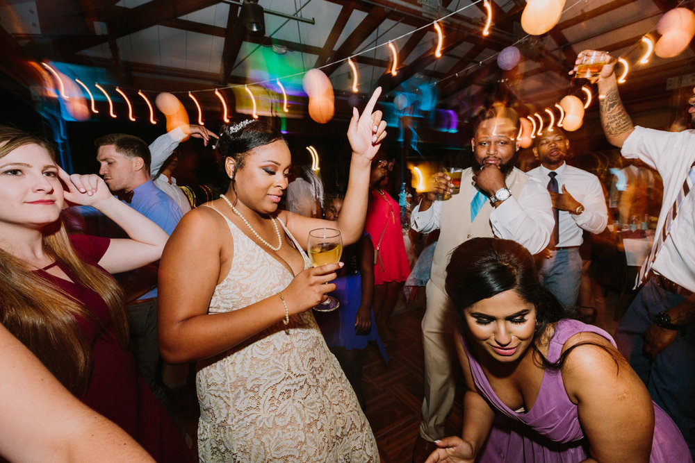 San Diego Tropical-Inspired Wedding janelle on dance floor with guests, lights blurred
