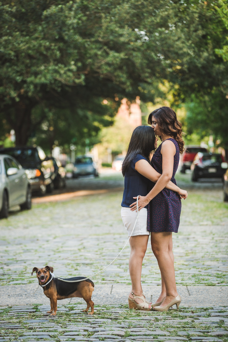 Wine Bar Engagement Virginia kiss on forehead on cobblestone street with their dog olga