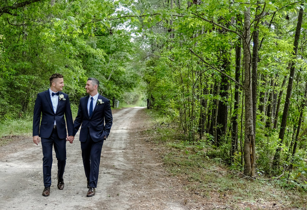Classic southern style wedding savannah georgia ben and peter walking down dirt path in forest holding hands