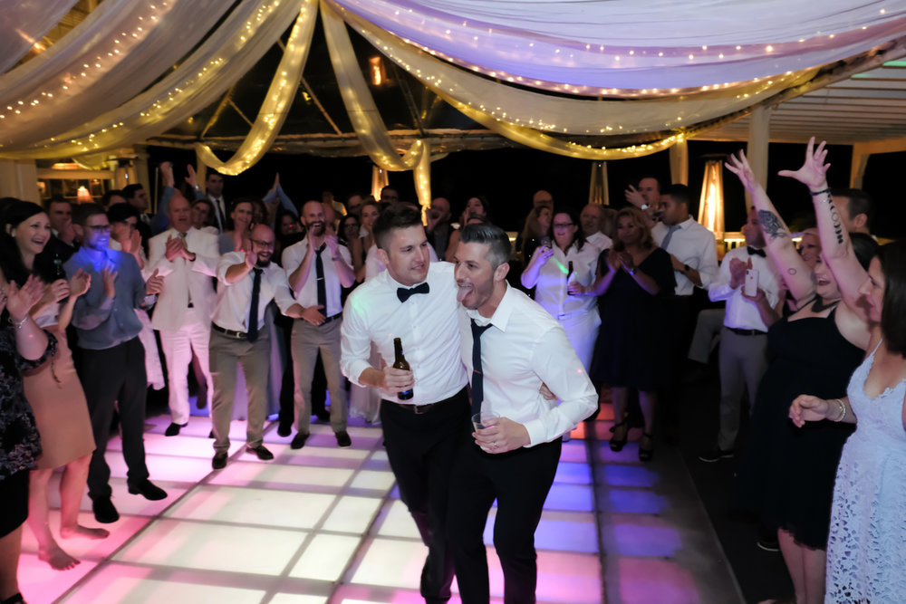 Classic southern style wedding savannah georgia grooms dancing together with guests surrounding them