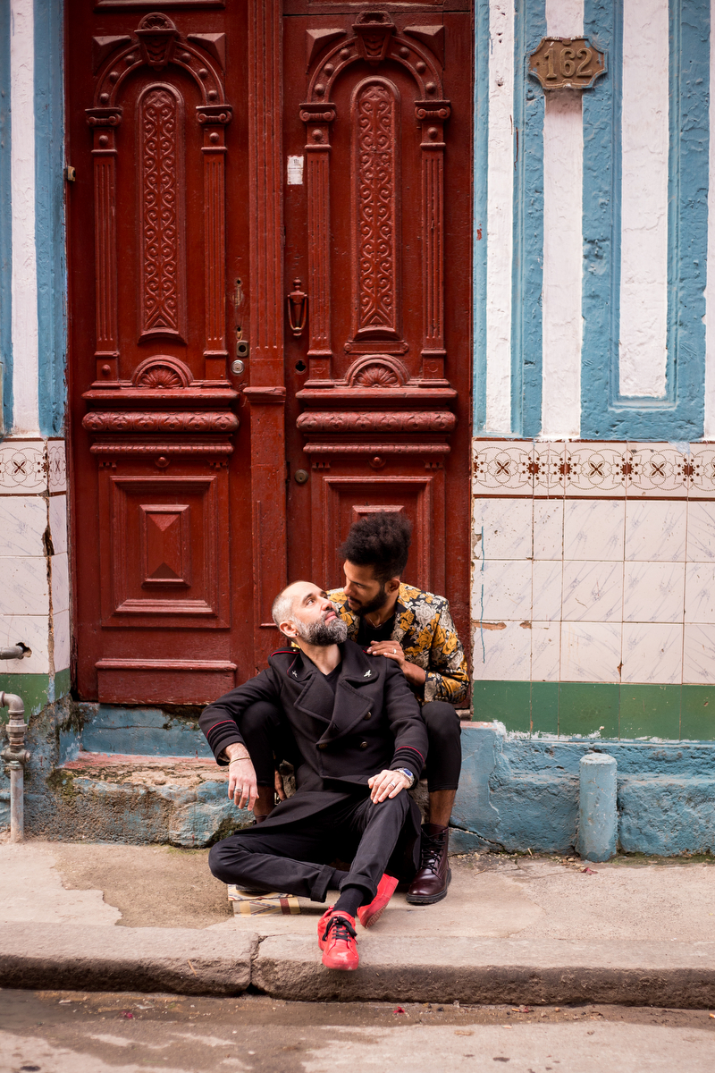 lovers in havana couple sitting on stoop gazing at one another