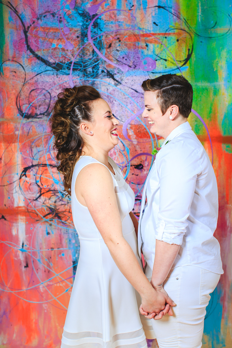 Love Out Loud Parker Colorado Styled Shoot couple gazing at each other holding hands in front of mural