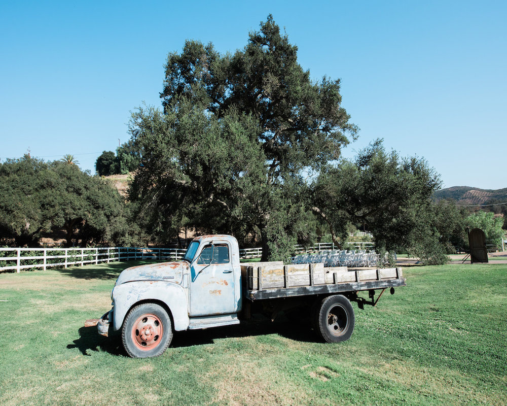 circle oak ranch farm wedding california classic truck parked on lawn with trees and fence in background