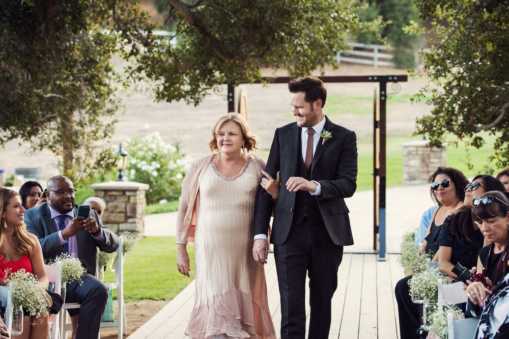 circle oak ranch farm wedding california groom walking down aisle with mother