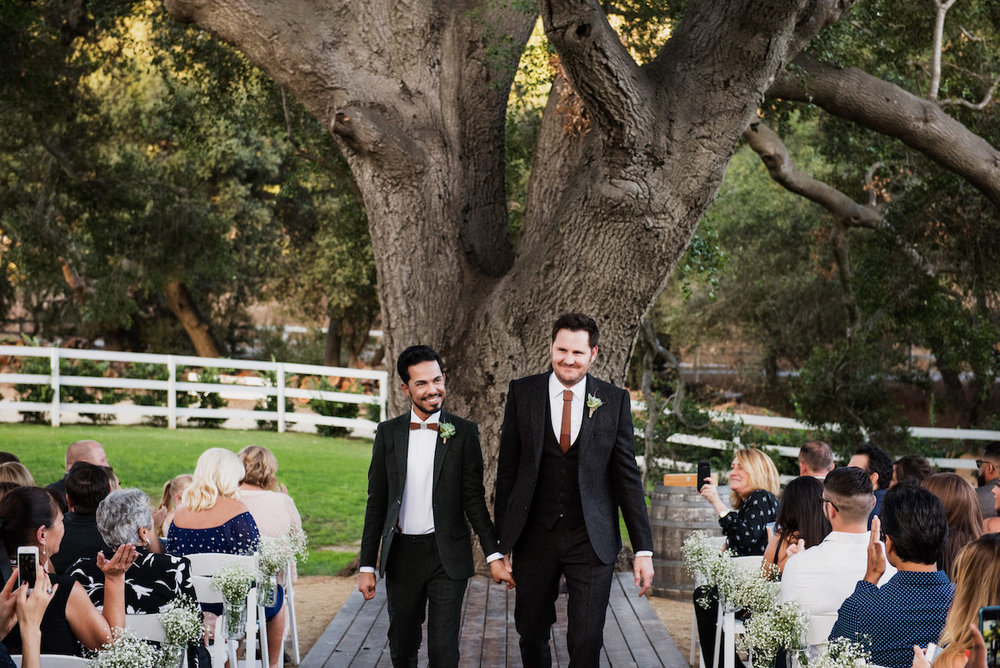 circle oak ranch farm wedding california newly married couple walking up aisle holding hands