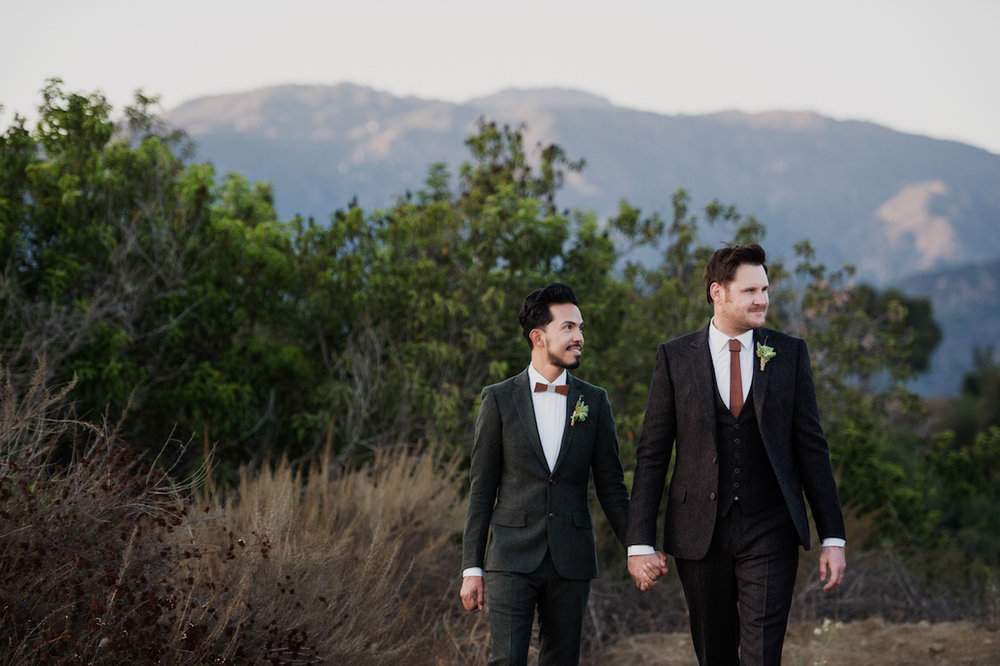 circle oak ranch farm wedding california couple holding hands in front of trees and distant mountains