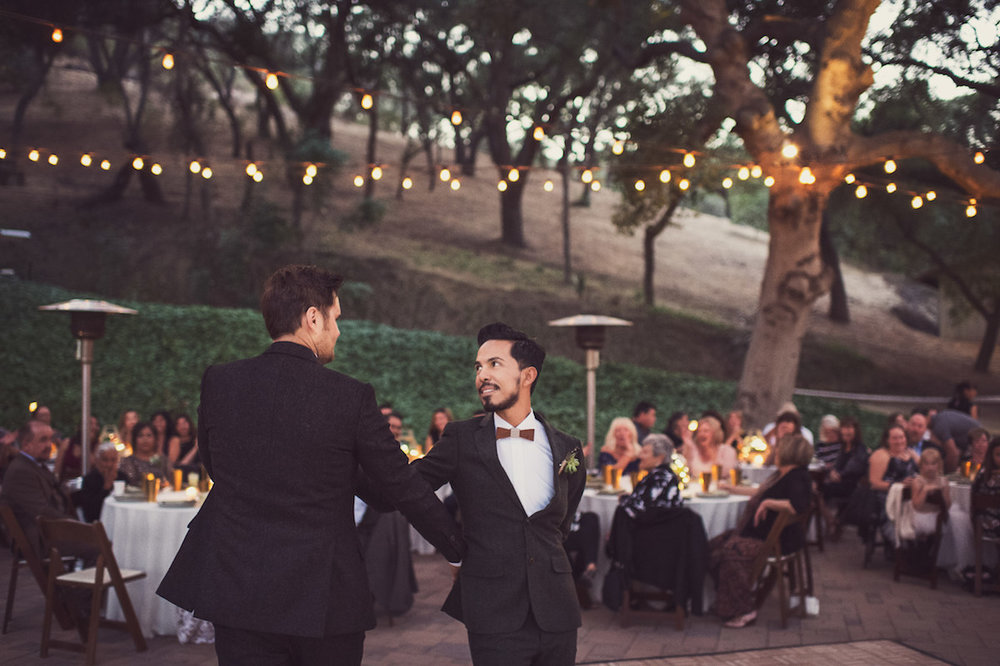 circle oak ranch farm wedding california casper and ulises on dance floor with guests watching and café lights surrounding outdoor reception area