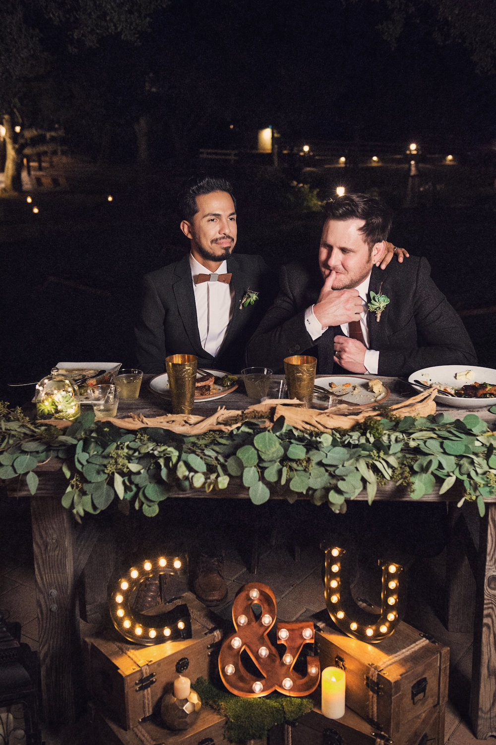 "circle oak ranch farm wedding california casper and ulises at head table with ""C & U"" lights in front on wooden trunks"