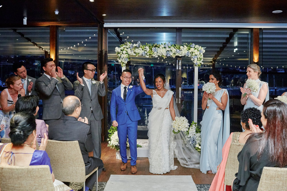 sri lankan, chinese, and harry potter wedding sydney australia hasara and daniel holding hands while guests clap