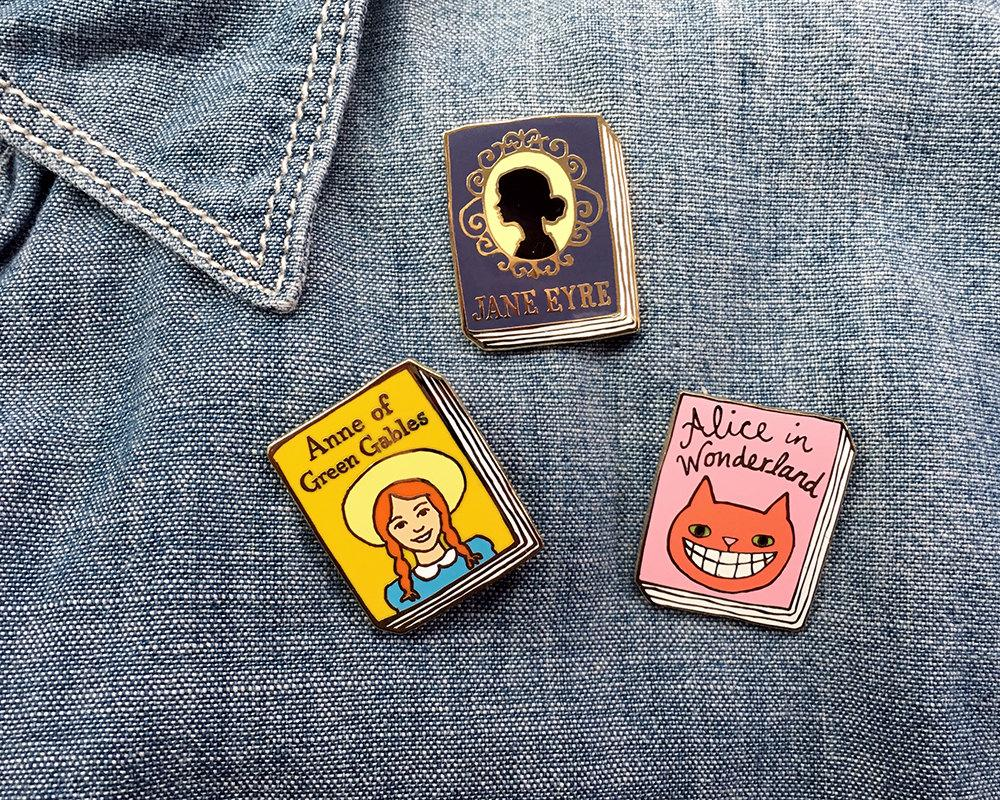 10 stylish gifts to give your wedding party Jane mount book pins: Anne of Green Gables, Alice and Wonderland, and Jane Eyre pinned to denim shirt