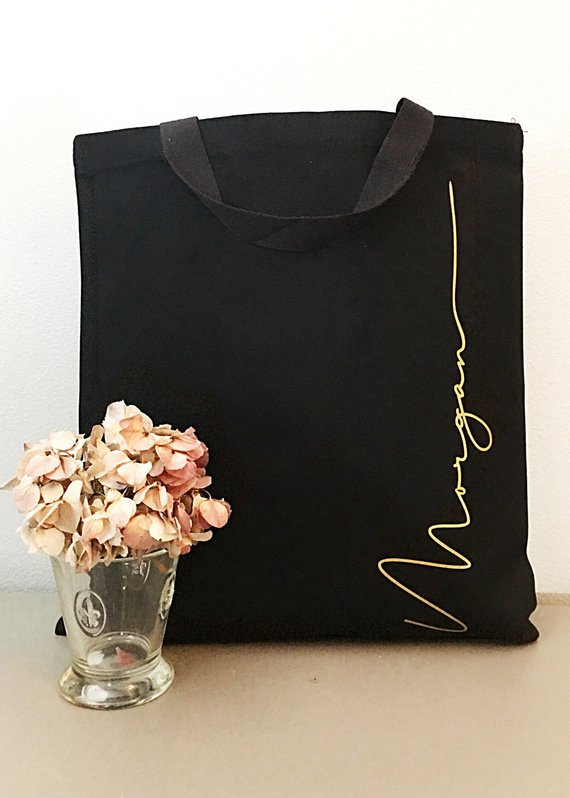 "10 stylish gifts to give your wedding party graceful greeting co. etsy shop black tote bag with the name ""morgan"" written in gold cursive script along one side, vase of flowers in front of bag"