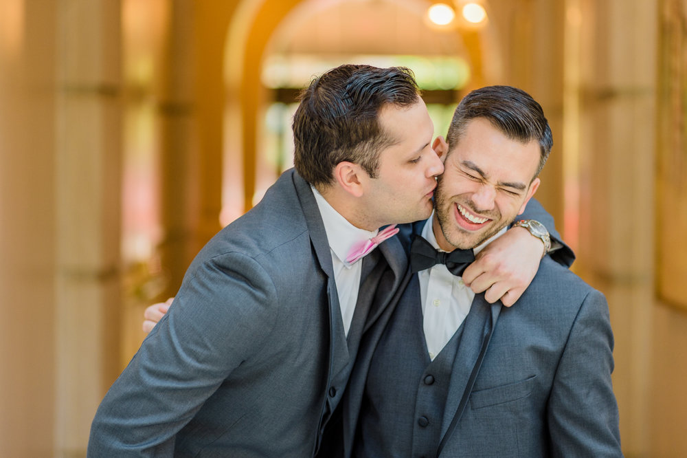 classic diverse wedding in washington dc kevin getting kiss on cheek from best man
