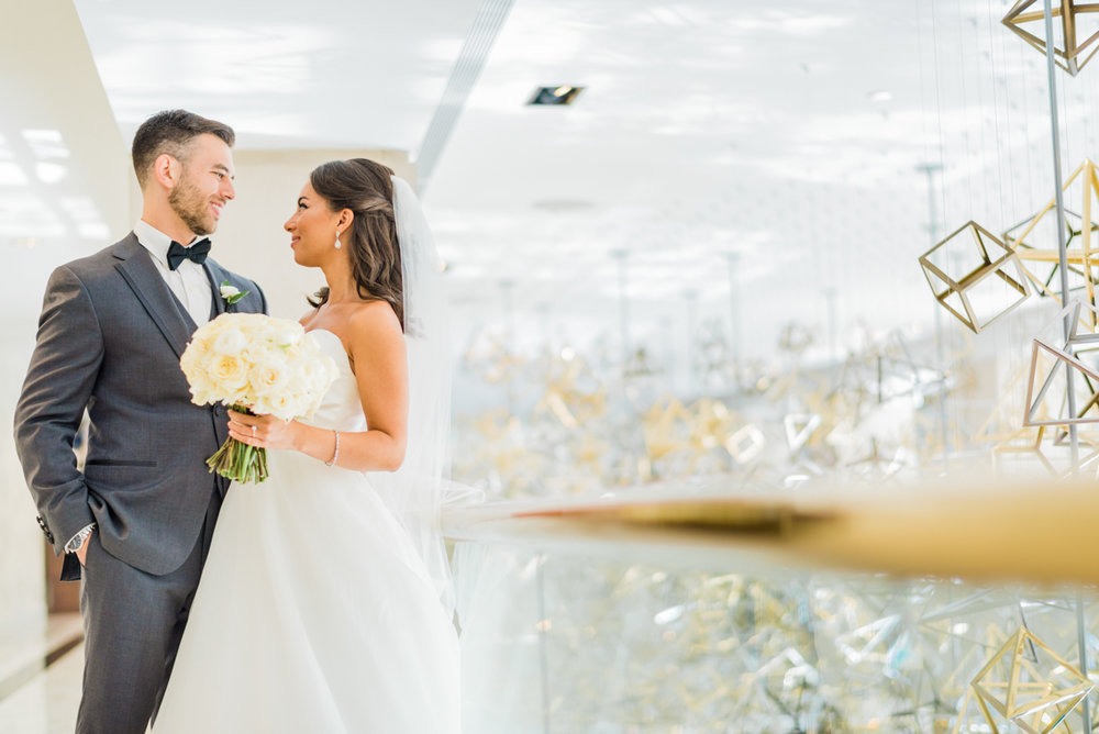 classic diverse wedding in washington dc couple by balcony with geometric art hanging from ceiling