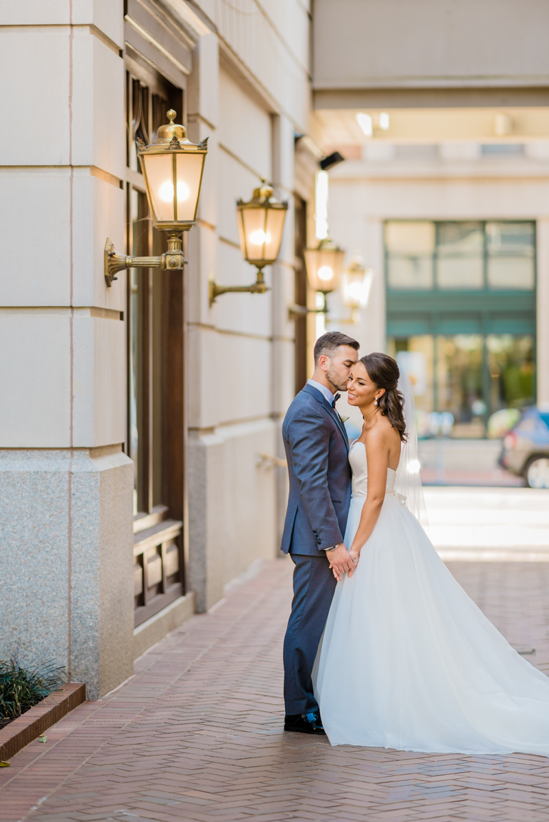 classic diverse wedding in washington dc kevin kissing zoe's cheek outside hotel on brick path