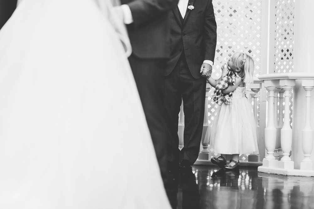 classic diverse wedding in washington dc younger flower girl holding groomsman's hand near altar during ceremony