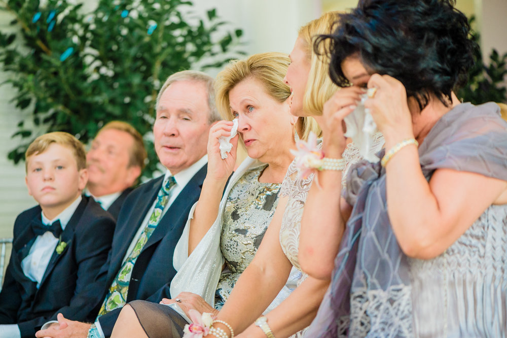 classic diverse wedding in washington dc close family in front row dabbing at tears during ceremony