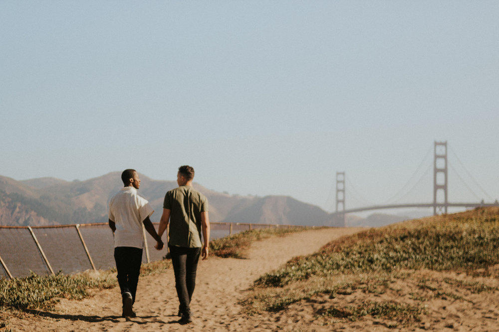 couples session baker beach san francisco california caleb and eugene walking hand in hand down sandy path with view of golden gate bridge
