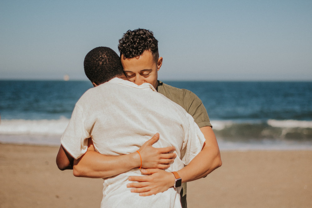 couples session baker beach san francisco california hug on beach with ocean in background