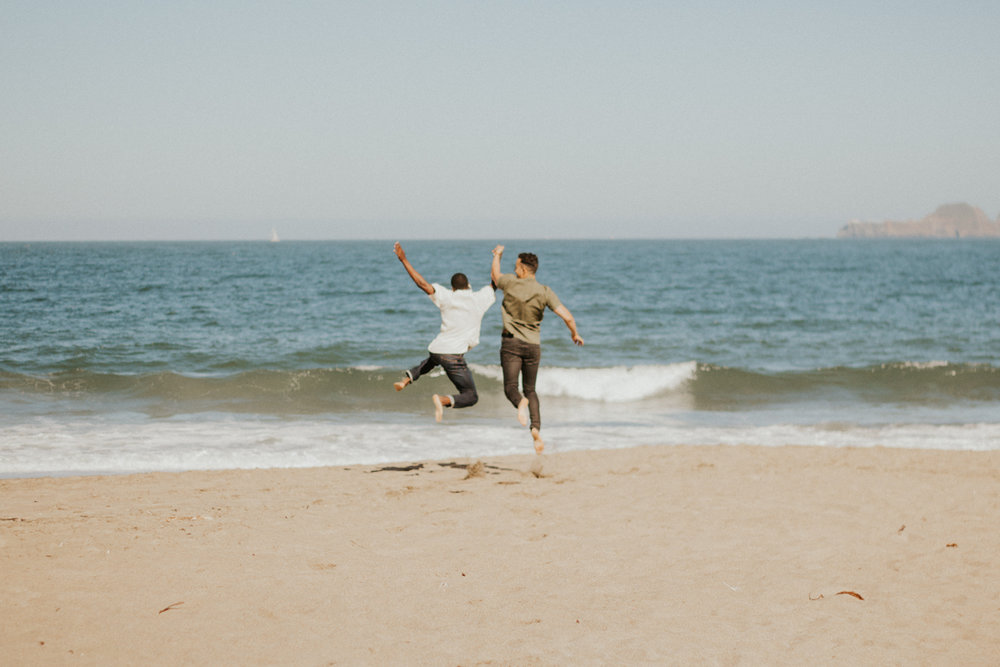 couples session baker beach san francisco california caleb and eugene leaping as they run toward the ocean holding hands